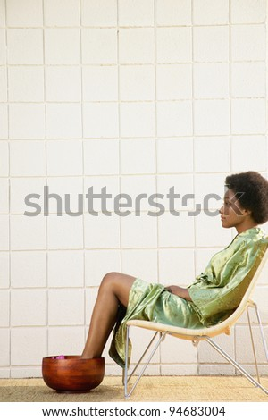 Profile of woman soaking her feet in bowl - stock photo