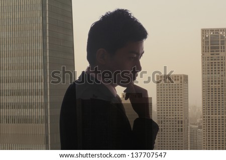 Profile of young businessman contemplating, double exposure of cityscape, Beijing