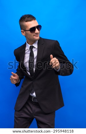 Profile of young man in sunglasses. Caucasian handsome man posing in fashionable business suit isolated on blue background. - stock photo
