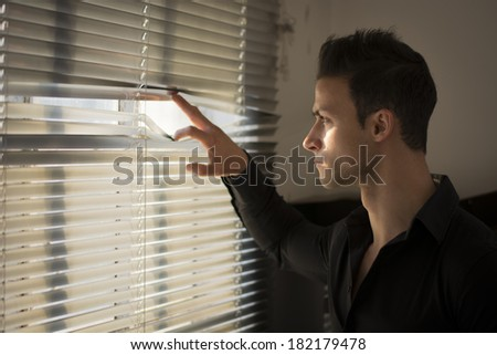 Profile of young man peeking through venetian blinds in a dark room - stock photo