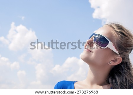 Profile of Young Smiling Caucasian Blond Female Wearing sunglasses and Looking Up. Horizontal Image Orientation