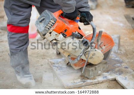 Profile on the blade of an asphalt or concrete cutter and workers boots .Construction worker using a concrete saw, cutting stones in a cloud of concrete dust for creating a track.. - stock photo