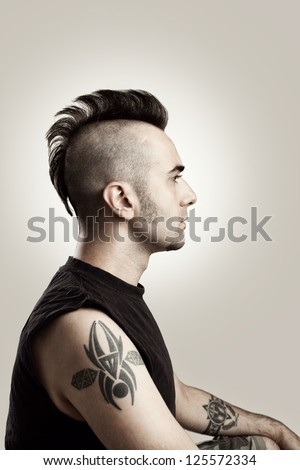 profile picture of a tattooed man with mohawk style hair - stock photo