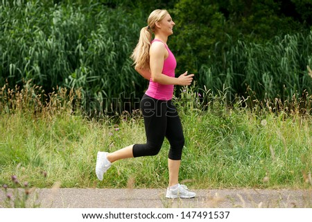 Profile portrait of a beautiful young woman running in the park