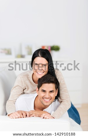 Profile portrait of a cheerful young couple lying on the sofa in their living room and smiling.