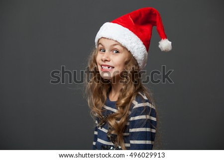 Profile portrait of a cute little girl in a christmas cap, gray background