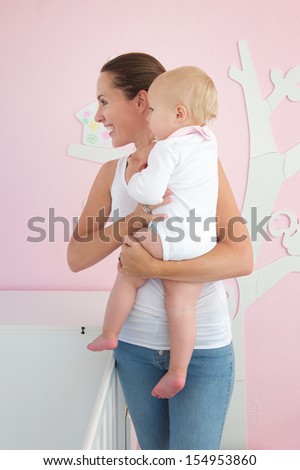 Profile portrait of a happy young woman holding cute baby and looking away