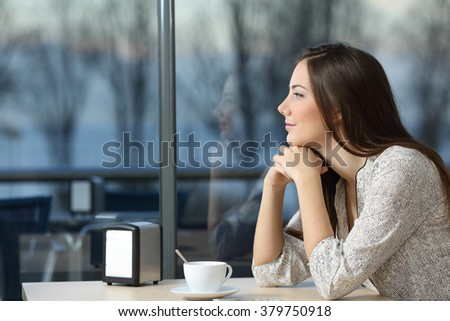 Profile portrait of a serious woman thinking in a coffee shop looking through the window in a bad day - stock photo