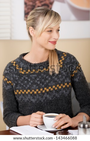 Profile portrait of a smiling beautiful blond woman drinking a cup of coffee in a coffee shop - stock photo