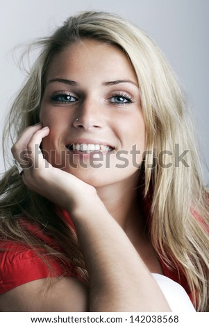 Profile portrait of a smiling young charming female model with her hand on the cheeks, isolated on white background.