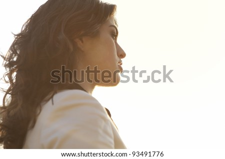 Profile portrait of a woman against the sky with sun rays bathing her face. - stock photo