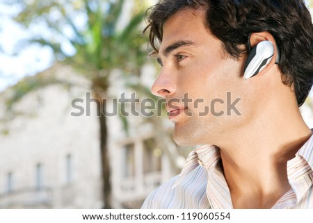 Profile portrait of a young attractive businessman using a hands free device to have a conversation on his cell phone while standing in front of classic office buildings in the city. - stock photo