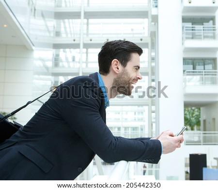 Profile portrait of a young businessman smiling and holding cellphone  - stock photo