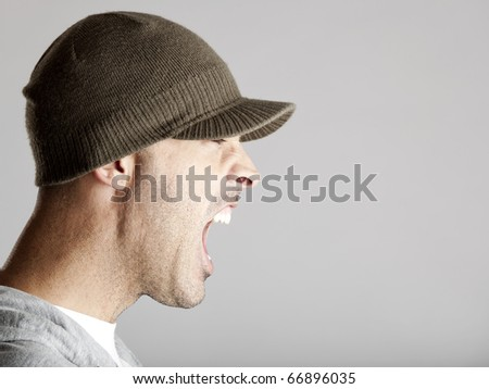Profile portrait of a young man yelling, isolated on a gray background - stock photo