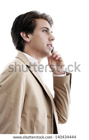 Profile portrait of a young sophisticated businessman talking on a mobile phone on a white background