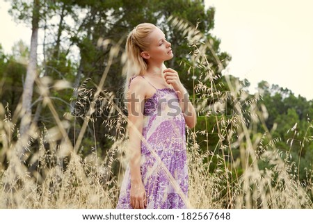 Profile portrait of an attractive blond woman relaxing taking a walk in the country, breathing fresh air and being thoughtful, enjoying a field of long yellow grass during a summer holiday, lifestyle. - stock photo