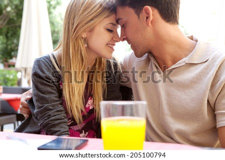 Profile portrait of an attractive young couple on holiday being romantic and holding their heads together while sitting at coffee terrace bar drinking refreshments during a summer vacation, outdoors. - stock photo