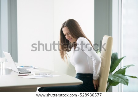 Profile portrait of an irritated young businesswoman woman at the office, feeling her back tired after working at laptop, uncomfortable chair, feeling severe back ache, itching, difficulty sitting