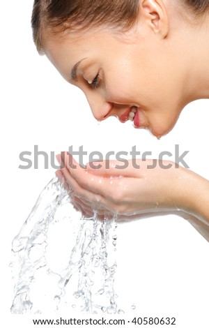 Profile portrait of an young female washing her face with clean water - stock photo