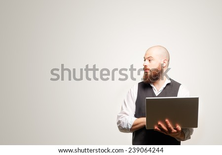 Profile portrait of bearded man in casual holding his laptop looking at copy space while standing against white background - stock photo