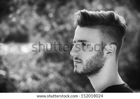 Profile portrait of handsome young man outdoors in nature, looking to a side, black and white shot - stock photo