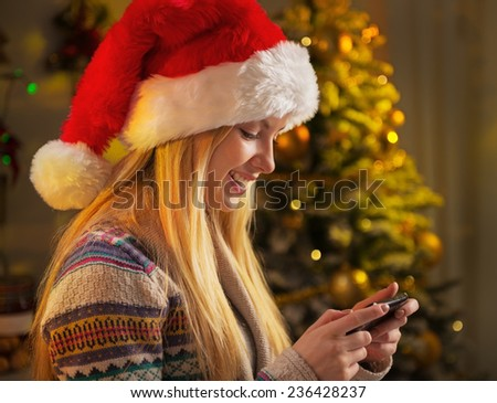 Profile portrait of happy teenager girl in santa hat writing sms