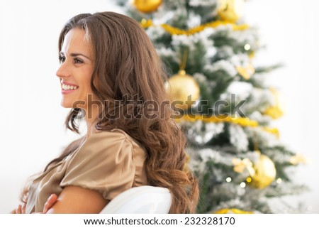 Profile portrait of happy young woman sitting near christmas tree - stock photo
