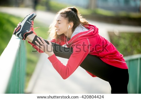 Profile portrait of sporty woman doing hamstring stretch in park after jogging. Female athlete runner getting ready for running routine on the bridge. Fit girl enjoying workout with closed eyes - stock photo