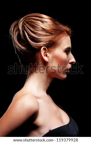 profile portrait of stylish woman with hairdo over dark background - stock photo