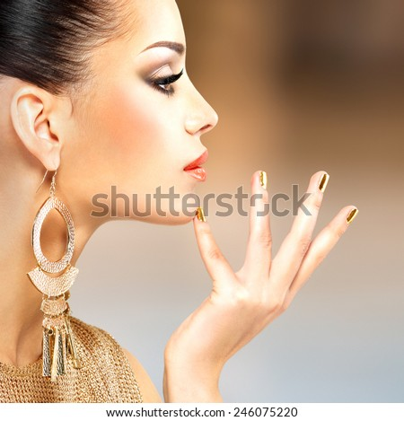 Profile portrait of the beautiful fashion woman with black makeup and golden manicure - stock photo