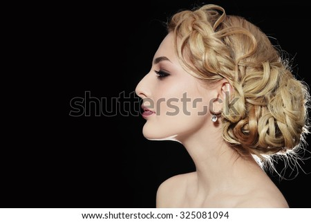 Profile portrait of young beautiful blonde woman with stylish prom hairdo - stock photo