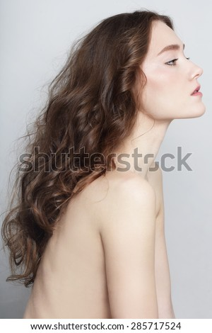Profile portrait of young beautiful slim girl with clear skin and long healthy curly hair - stock photo