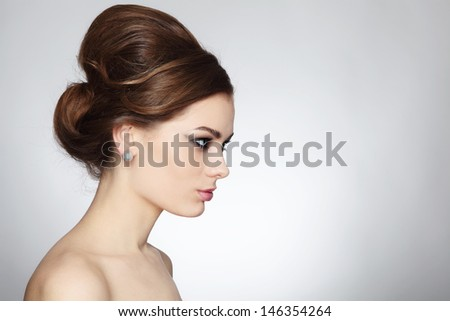 Profile portrait of young beautiful woman with stylish hair bun - stock photo