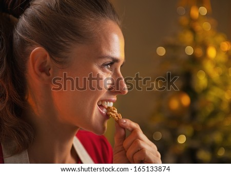 Profile portrait of young housewife eating walnuts