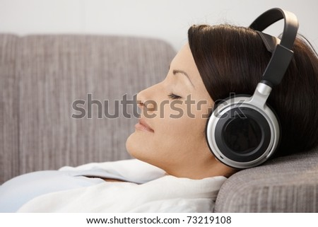 Profile portrait of young woman listening music, lying on sofa at home.?
