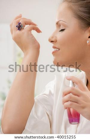 Profile portrait of young woman wearing white silk bathrobe applying perfume. - stock photo