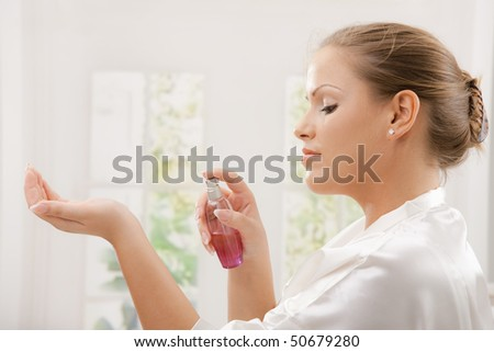 Profile portrait of young woman wearing white silk bathrobe applying perfume. - stock photo