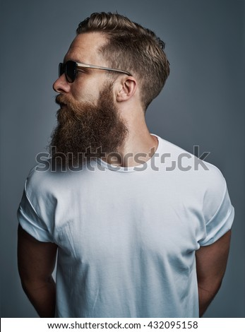 Profile portrait on turned head and long well trimmed beard of handsome man with sunglasses and white short sleeve shirt - stock photo