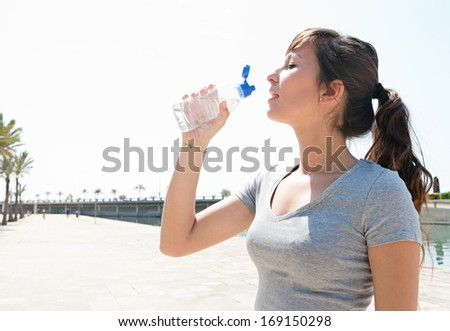 Profile portrait view of a young sporty woman drinking mineral water from a plastic bottle and getting refreshed after exercising outdoors during a sunny summer day.  - stock photo