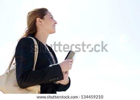 Profile portrait view of a young successful businesswoman carrying work folders and wearing a black suit, looking ahead against a blue sky, smiling. - stock photo