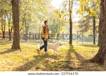 Profile shot of a cheerful young man walking his dog in a park on a sunny autumn day - stock photo