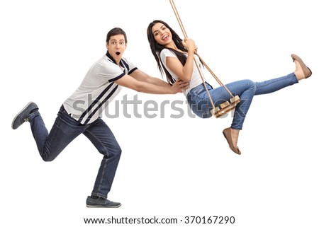 Profile shot of a delighted young man pushing his girlfriend on a swing isolated on white background - stock photo