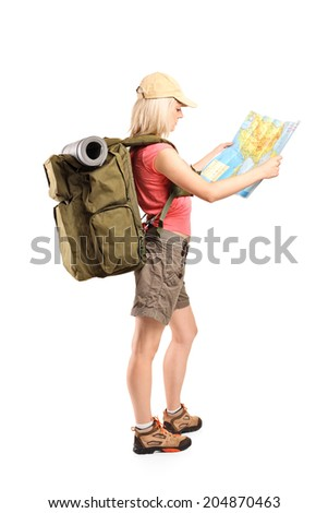 Profile shot of a female tourist looking at a map isolated on white background