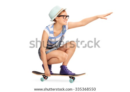 Profile shot of a hipster girl riding a skateboard and pointing forward with her hand isolated on white background - stock photo
