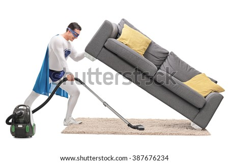 Profile shot of a strong man in superhero costume vacuuming under a sofa isolated on white background - stock photo