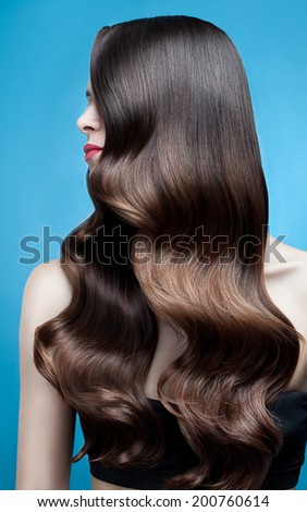 Profile shot of a woman with long glossy curly hairstyle - stock photo