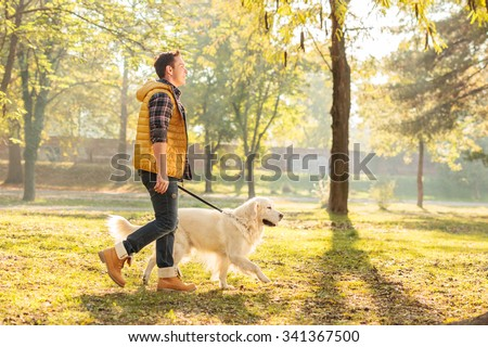Profile shot of a young guy walking his dog in a park on a sunny autumn day - stock photo