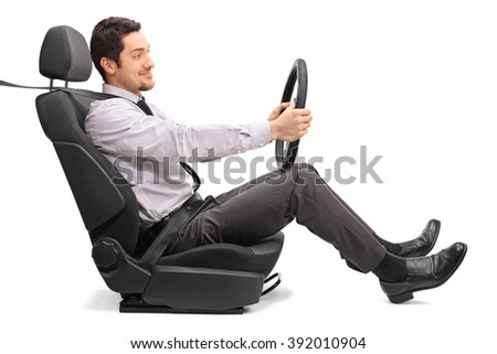 Profile shot of a young man holding a steering wheel seated on a car seat isolated on white background - stock photo