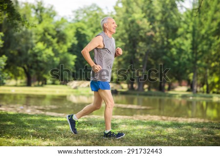 Profile shot of an active senior jogging in a park and listening to music on headphones