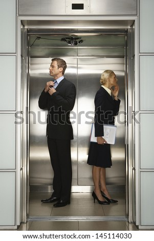 Profile shot of businessman and businesswoman preparing for interview in office elevator - stock photo